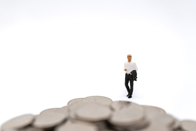 Business, money investment and planning concept. businessman miniature figure people figure walking to pile of silver coins on white background.