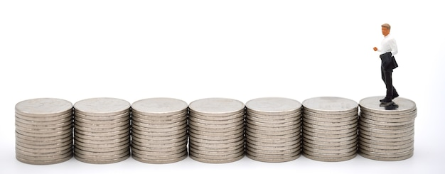Business, money investment and planning concept. businessman miniature figure people figure walking on row of stack of silver coins on white background.