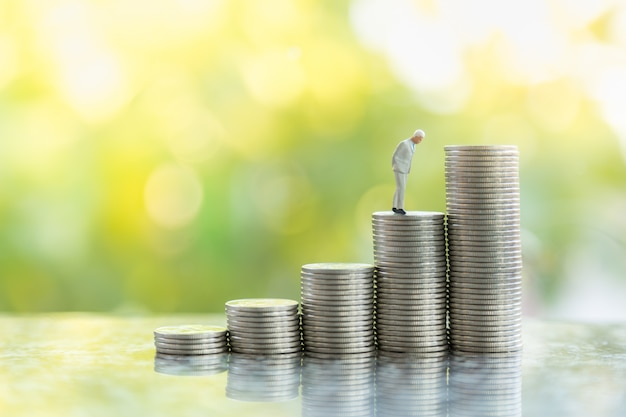 Business, money investment and planning concept.  close up of businessman miniature people figure standing on stack of silver coins with green anture background with copy sapce.