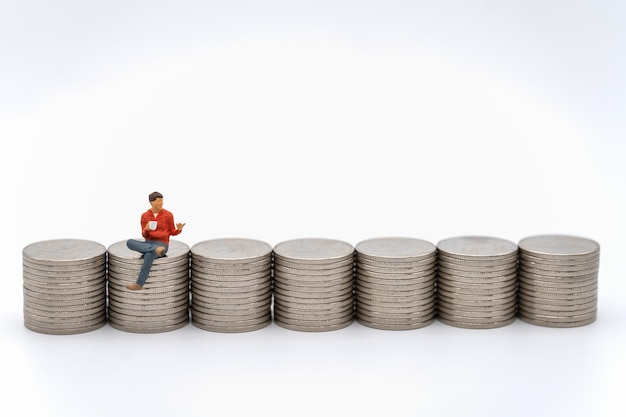 Business, money investment and planning concept. closeup of male miniature figure people with cup of coffee sitting on stack of silver coins on white background.