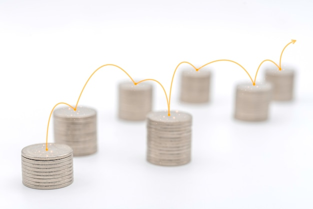 Business money and planning concept. closeup of stack of silver coins with red line to connect each stack on white background.