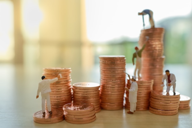 Business, money, planning and saving concept. close up of group of worker cleaning and painting stack of coin.