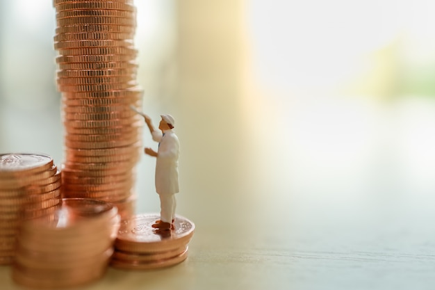 Business, money, planning and saving concept. close up of worker painting stack of coins on wooden table with copy space.