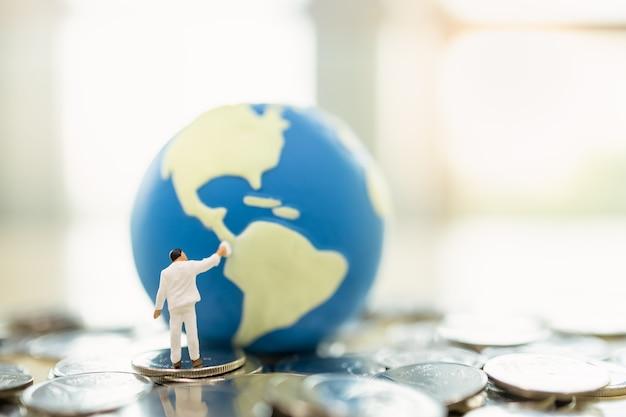 비즈니스, 돈은 지구와 글로벌 개념을 저장합니다. 작업자 미니어처는 복사 공간이 있는 동전 더미에 미니 세계 공을 청소하고 페인팅하는 사람들을 나타냅니다.