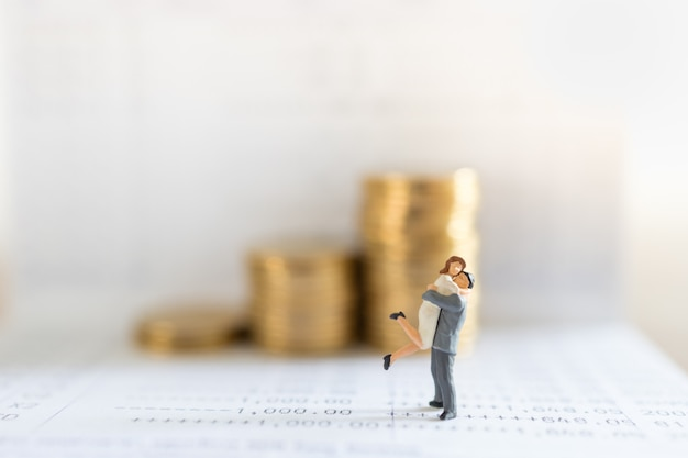 Business, money, saving, security and couple family concept. close up of man and woman miniature figure people hug and standing on bank passbook with stack of gold coins in background and copy space.