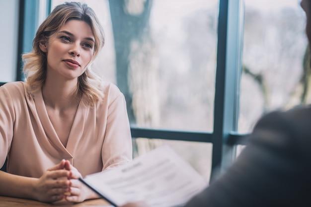 商談。パートナーと通信するオフィスのテーブルに座って楽観的な気分で美しい若いビジネスウーマン