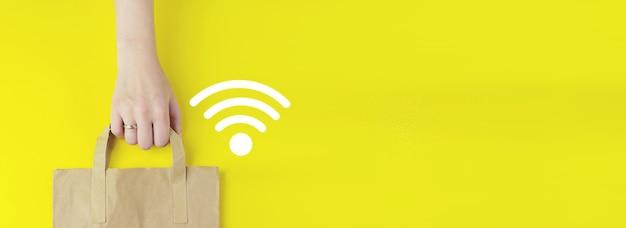 Бизнес-концепция сетевого подключения. сумка для покупок из переработанной коричневой бумаги в руке с голограммой wi-fi на желтом фоне, плоская планировка. концепция летней распродажи. концепция службы доставки.