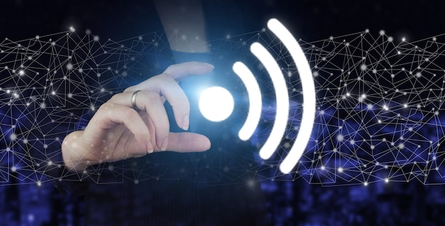 Business networking connection concept and wi-fi in city. hand hold digital hologram wi fi sign on city dark blurred background.