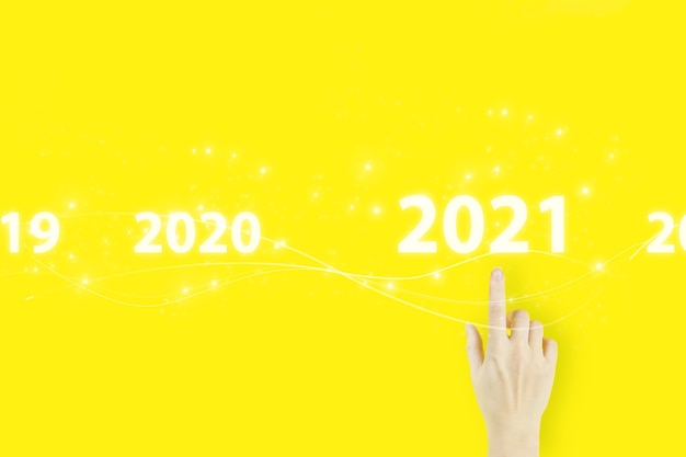 Business new year card concept. young woman's hand pointing finger with hologram 2021 sign on yellow background.