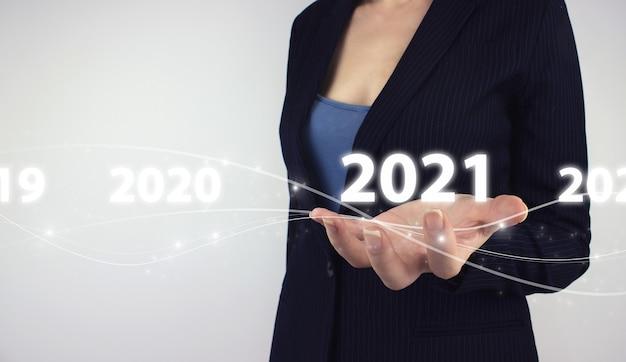 年賀状の概念。灰色の背景にデジタルホログラム2千21年を手に持ってください。 2021年の新しいスマートテクノロジー、および2021年の新しいテクノロジーのトレンド。