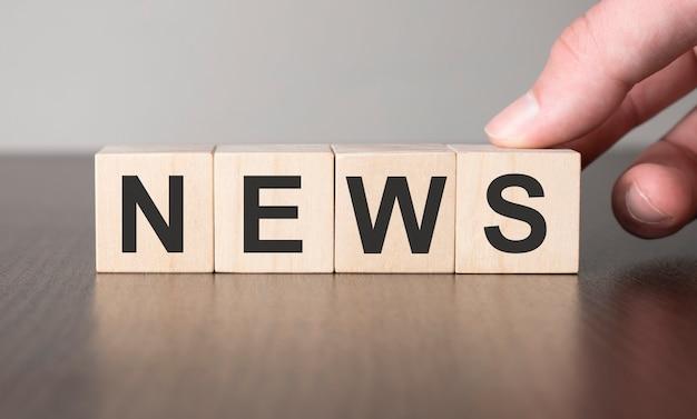 Концепция деловых новостей. рука и подделка на деревянном кубическом блоке.