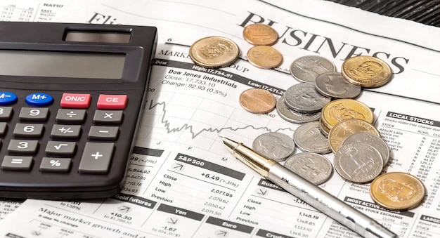 Business newspaper with calculator and coins