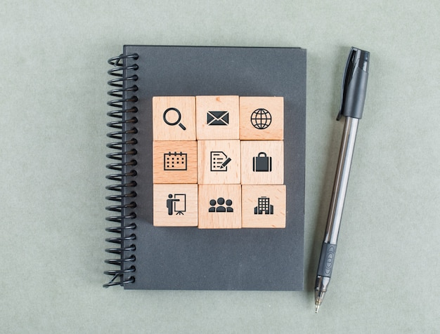 Business notes concept with wooden blocks with icons, notebook, pencil on sage color table top view.