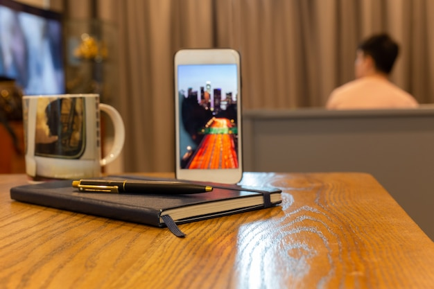 Business object cell phone with notebook and pen on wooden table