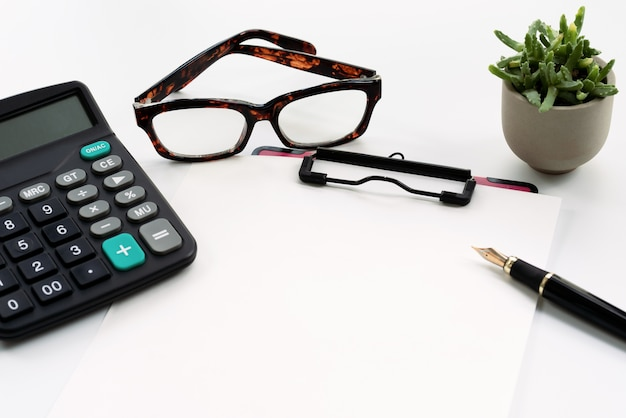 Business objects, clipboard with blank sheet of paper, pen, glasses and calculator