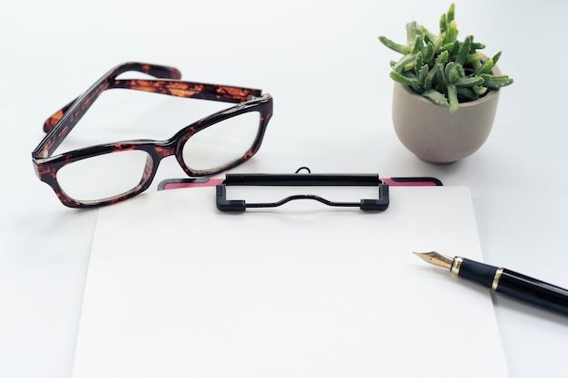 Business objects, clipboard with blank sheet of paper, pen, glasses on white background