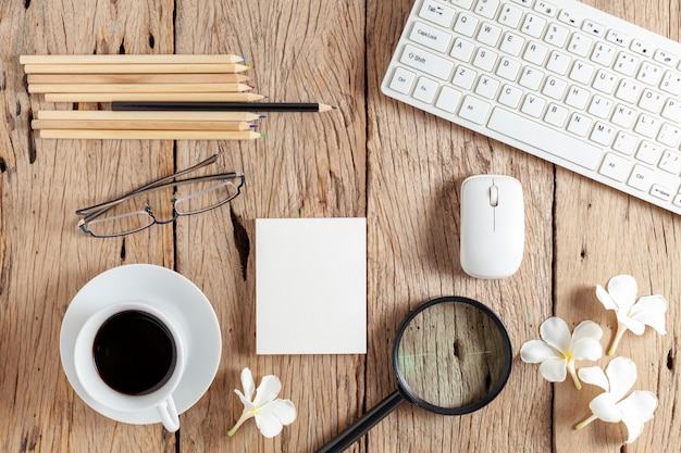 Business objects of keyboard, mouse, white coffee cup, white paper, pencils, glasses, magnifying glass