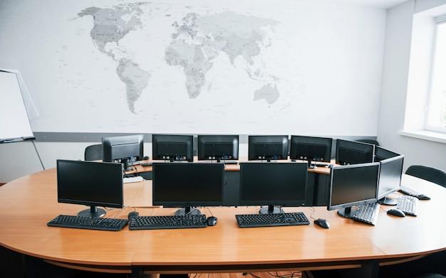 많은 컴퓨터 화면과 함께 낮에 비즈니스 사무실. 벽에지도