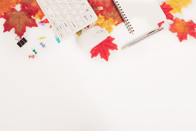 Business office desk in autumn season concept with colorful maple leaves and stationaries, on white