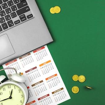 노트북과 달력이 있는 비즈니스 사무실 책상에는 돈, 금화, 시간은 돈 개념 사진