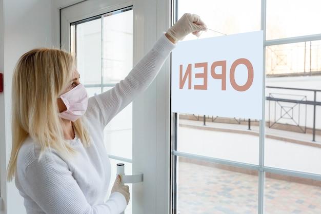 신종 코로나바이러스(covid-19) 대유행의 영향으로 비즈니스 사무실이나 상점이 파산한 비즈니스를 폐쇄했습니다. 마스크를 쓴 신원 미상의 사람이 정문 배경에 닫힌 표지판을 걸고 있습니다.