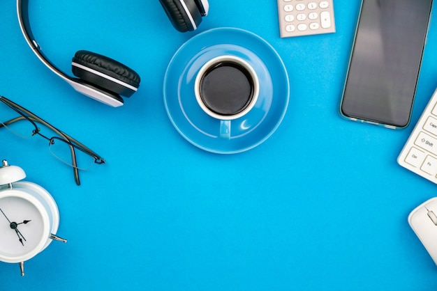 Business office table with business objects of smartphone headphone alarm clock and coffee cup.