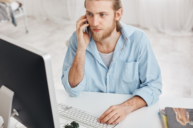 Business, office and technology concept. top view of bearded employee wearing blue shirt, talking on phone with companions, typing on keyboard, looking on computer screen, using modern devices