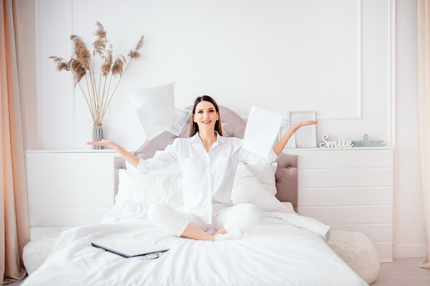 Business, office, victory, achievement and education concept - woman sitting on bed threw documents, rejoices at work completion