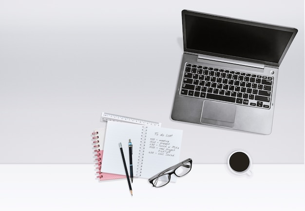Business office workplace concept. laptop with notebook with task list and coffee cup.