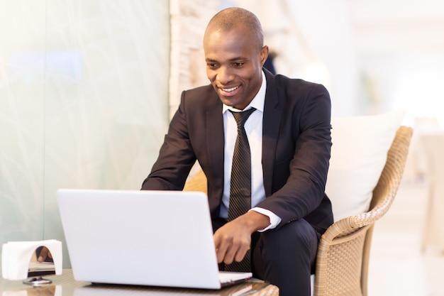 이동 중에도 비즈니스. 레스토랑에 앉아 노트북을 사용하는 쾌활한 젊은 아프리카 사업가