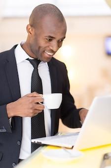 이동 중에도 비즈니스. 바에 서 있는 동안 노트북을 사용하는 쾌활한 젊은 아프리카 사업가
