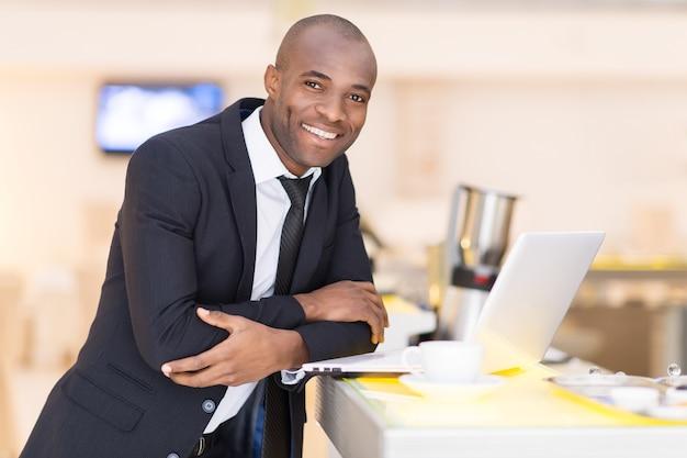 이동 중에도 비즈니스. 바에 기대어 있는 동안 노트북을 사용하는 정장 차림의 쾌활한 젊은 아프리카 남자