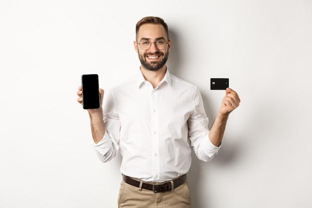 Pagamento aziendale e online. uomo bello sorridente che mostra schermo mobile e carta di credito, in piedi