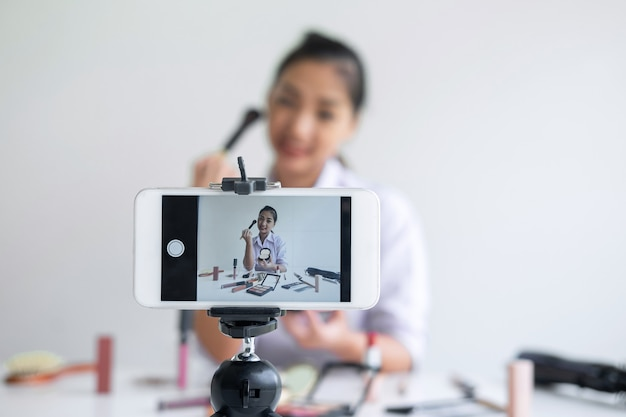 Business online on social media, beautiful asian woman blogger is showing present tutorial beauty cosmetic product and broadcast live streaming video to social network while recording teaching online