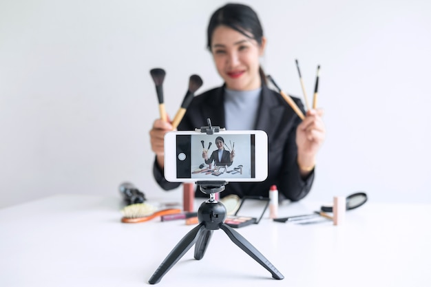 Business online on social media, beautiful woman blogger is showing present tutorial beauty cosmetic product and broadcast live streaming video to social network while recording teaching online