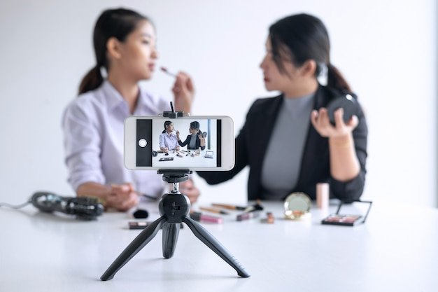 Business online on social media, two beautiful woman blogger is showing present tutorial beauty cosmetic product and broadcast live streaming video to social network while recording teaching online