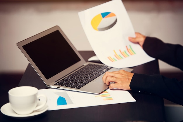時間に対して情報チャートに人差し指を保持しているビジネスまたは働く人