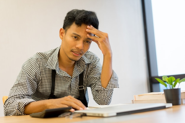 Business owner asian man stress headache with debt