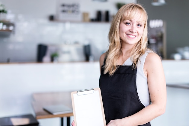 Business owner caucasian woman is holding menu wear apron with coffee shop background