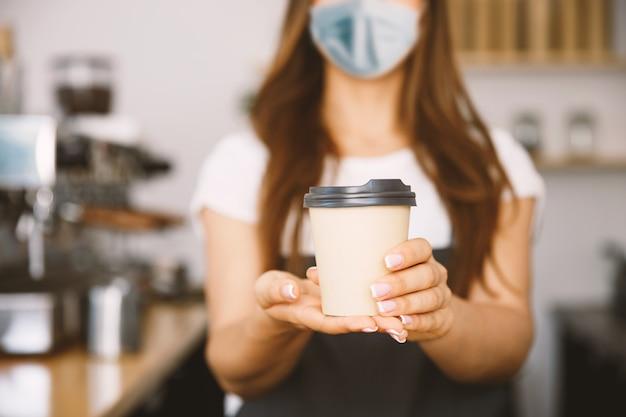 Концепция владельца бизнеса - красивая кавказская бариста в лицевой маске предлагает одноразовый горячий кофе на вынос в современном кафе