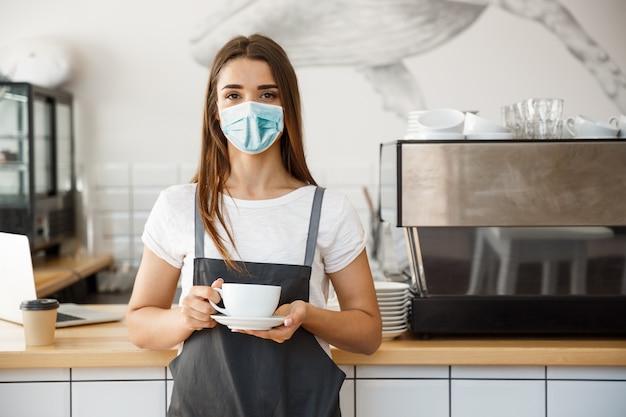 Концепция владельца бизнеса - красивая кавказская бариста в маске предлагает горячий кофе в современной кофейне