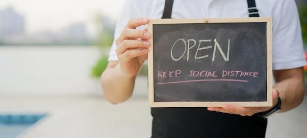 사업 소유자 남자는 코로나 바이러스 전염병 후 재개를 홍보하고 알리기 위해 열린 사인 보드를 개최합니다.