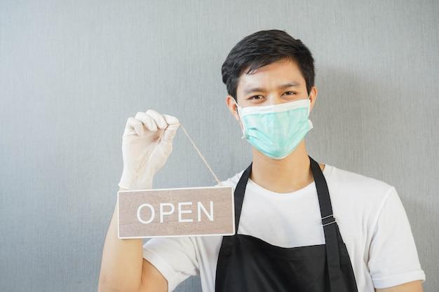 Мужчина-владелец бизнеса держит открытую доску, чтобы продвигать открытие магазина