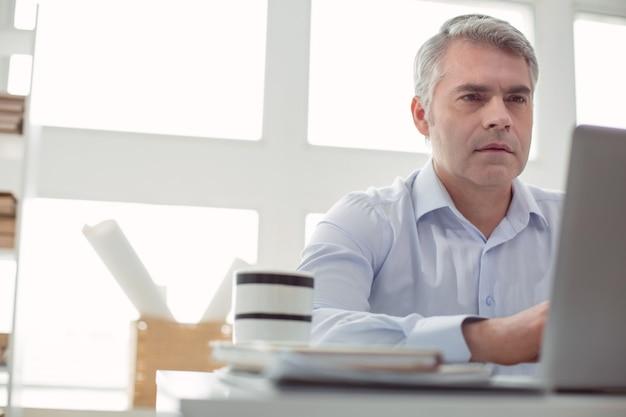 事業主。ノートパソコンの画面を見て、仕事中にそれに取り組んでいるスマートなハンサムな大人の男