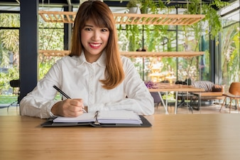 Business owner writing notebook sit on chair in front of the coffee shop with a smile