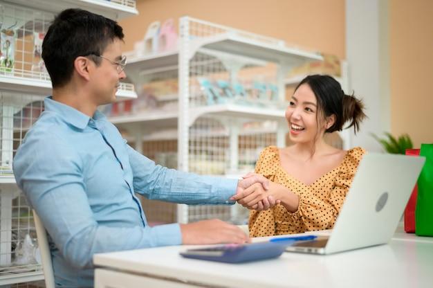 経営者はビジネスデータを分析し、現代の店で話し、笑顔を見せています