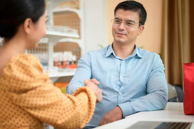 Владельцы бизнеса анализируют бизнес-данные, разговаривают и улыбаются в современном магазине
