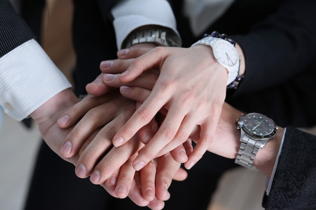 Business partneers putting hands one on one