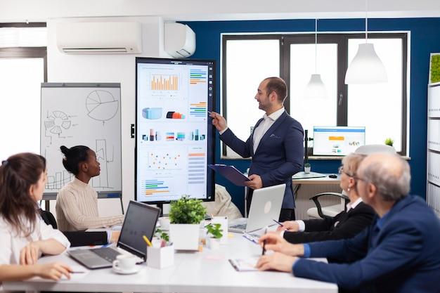 新しいスタートアップオフィスでブレーンストーミングを行う多様なチームに会社の戦略を提示し、財務グラフを分析するビジネスパートナー