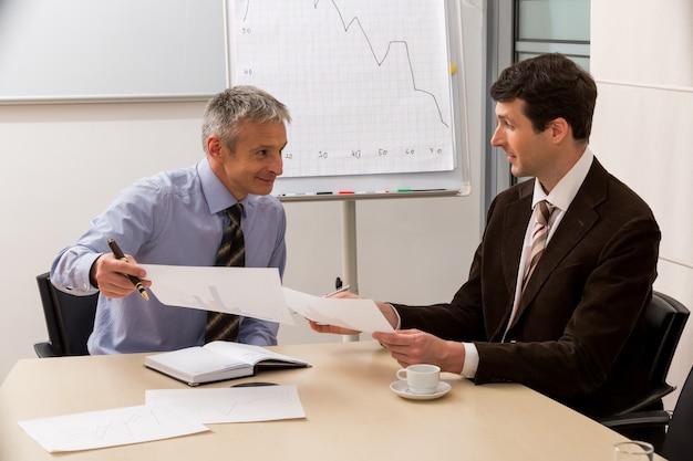 Деловые партнеры обсуждают успешный проект на встрече с начальством в офисе